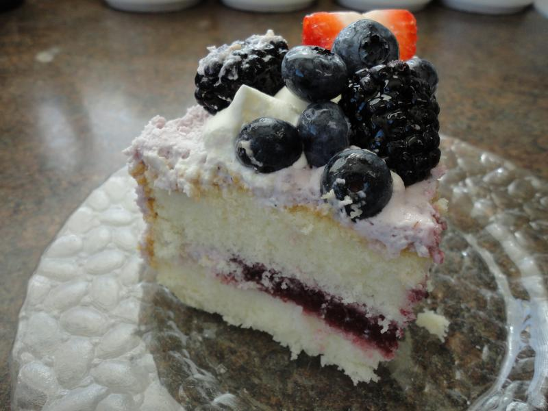 A delicious looking layered white cake with berries and whip cream.
